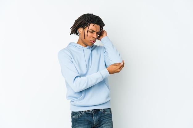 Молодой афро-американский мужчина раста массирует локоть, страдая после плохого движения.