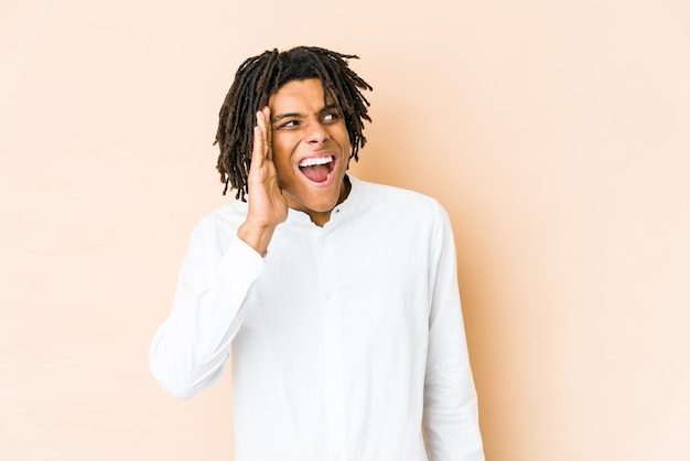 Молодой афро-американский раста-мужчина кричит возбужденно.