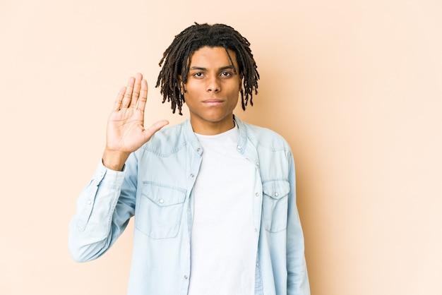 陽気な笑顔の若いアフリカ系アメリカ人のラスタ男は、指で5番を示しています。