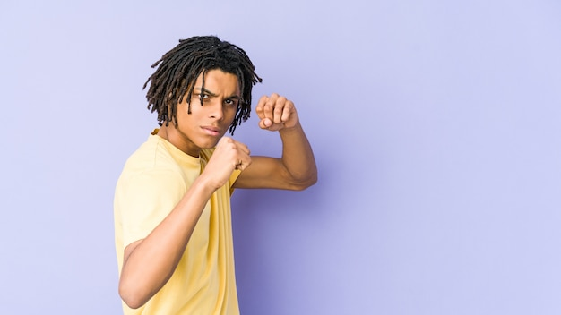 Young african american rasta man throwing a punch, anger, fighting due to an argument, boxing.
