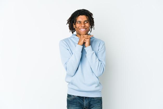 若いアフリカ系アメリカ人のラスタマンはあごの下に手を保ち、幸せそうに脇を見ています。