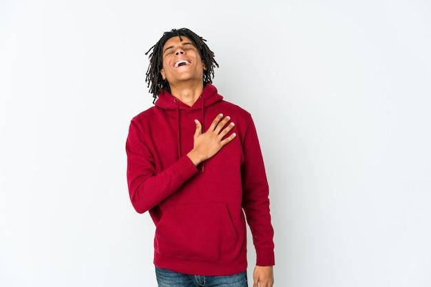 若いアフリカ系アメリカ人のラスタマンは、胸に手を置いて大声で笑います。