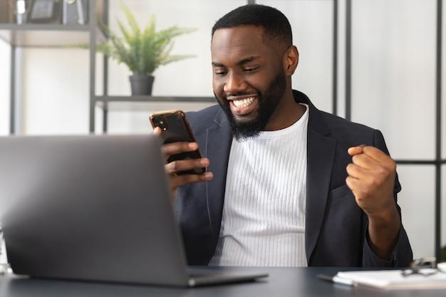 スマートフォンで予期しない良いニュースを読んで若いアフリカ系アメリカ人