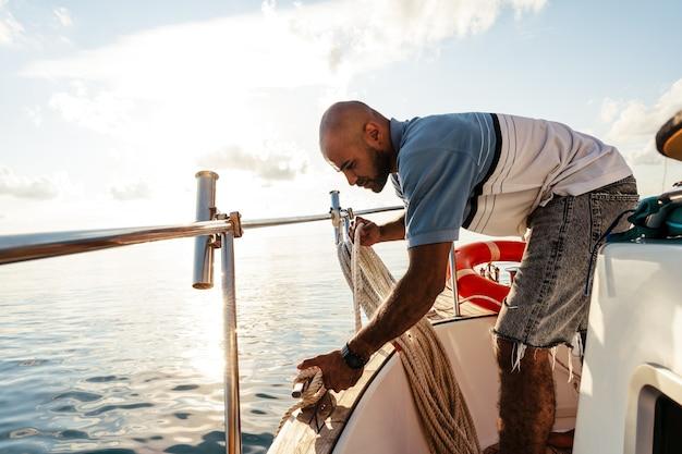 일몰에 바다에서 요트에 밧줄을 묶는 젊은 아프리카계 미국인 선원, 클로즈업