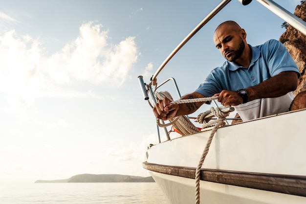 日没の海でヨットにロープを結ぶ若いアフリカ系アメリカ人の船乗り