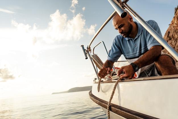 일몰에 바다에서 요트에 밧줄을 묶는 젊은 아프리카계 미국인 선원