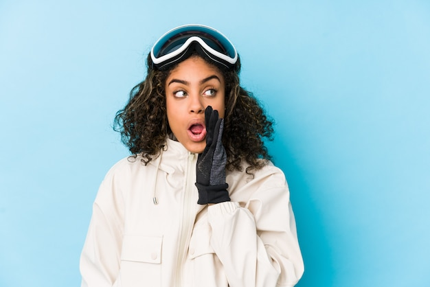 Young african american skier woman isolated is saying a secret hot braking news and looking aside