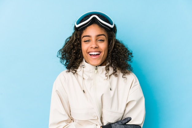 Young african american skier woman isolated laughing and having fun.