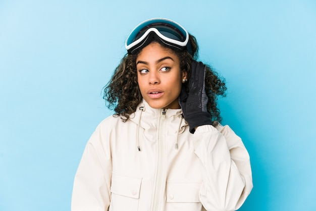 Young african american skier woman isolated trying to listening a gossip.