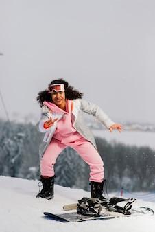 Молодая афро-американская лыжница со сноубордом улыбается и поднимает палец вверх