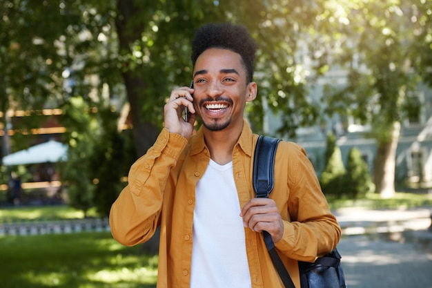 Young african american smiling boy walking afterr study in the park, talking on the phone, wears in a yellow shirt and a white t-shirt with a backpack on one shoulder, smiling and enjoys the day.