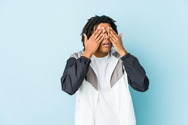 Молодой афро-американский спортивный человек боится закрывать глаза руками.
