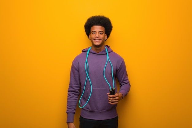 Young african american sport man holding a jump rope cheerful with a big smile