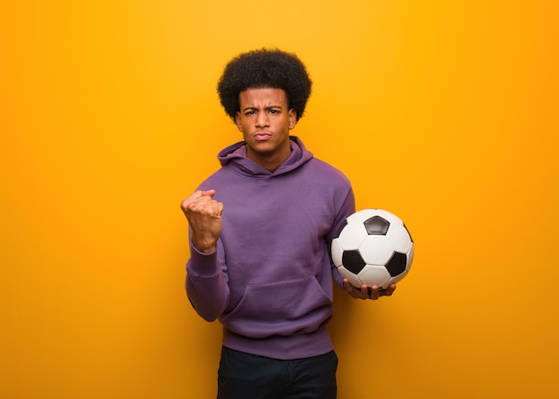 Young african american sport man holding a soccer ball showing fist to front, angry expression