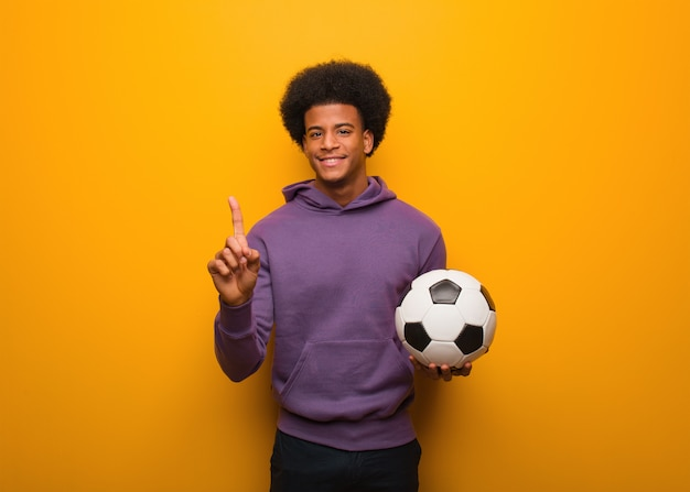 Young african american sport man holding a soccer ball showing number one
