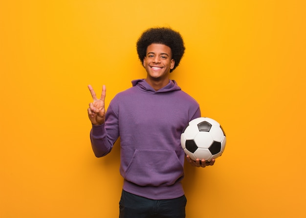 Young african american sport man holding a soccer ball showing number two