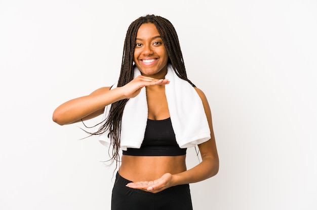 Young african american sport woman isolated holding something with both hands, product presentation.