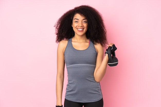 Kettlebell와 역도를 만드는 분홍색에 고립 된 젊은 아프리카 계 미국인 스포츠 여자