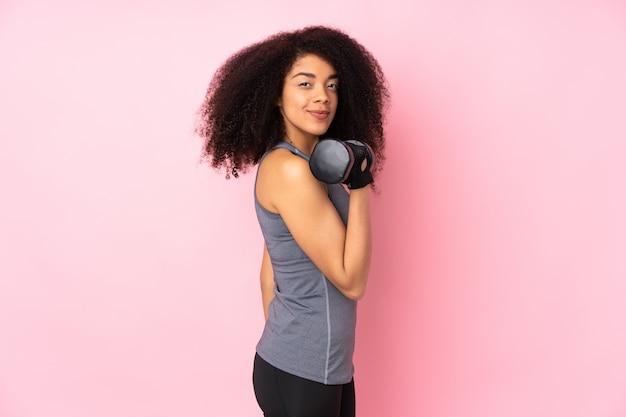 重量挙げを作るピンクに分離された若いアフリカ系アメリカ人スポーツの女性