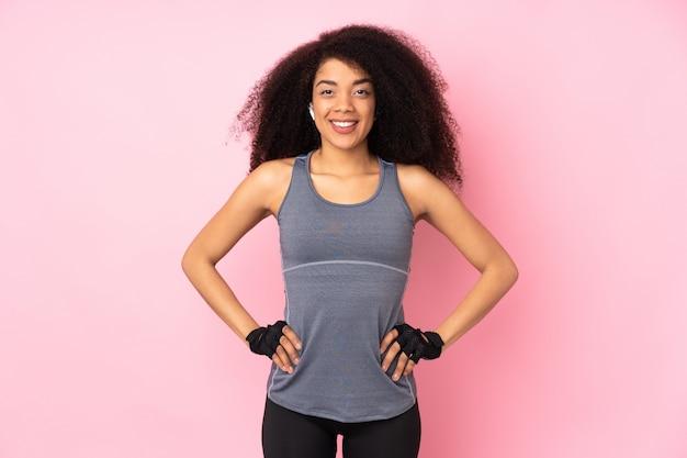 若いアフリカ系アメリカ人のスポーツ女性が腰に腕でポーズと笑顔のピンクの分離