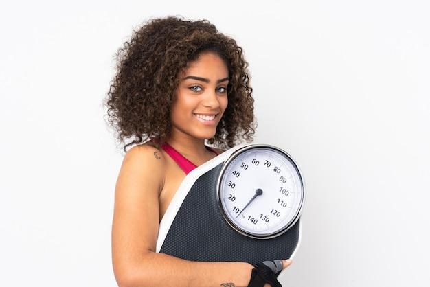 計量機を白で隔離される若いアフリカ系アメリカ人スポーツの女性