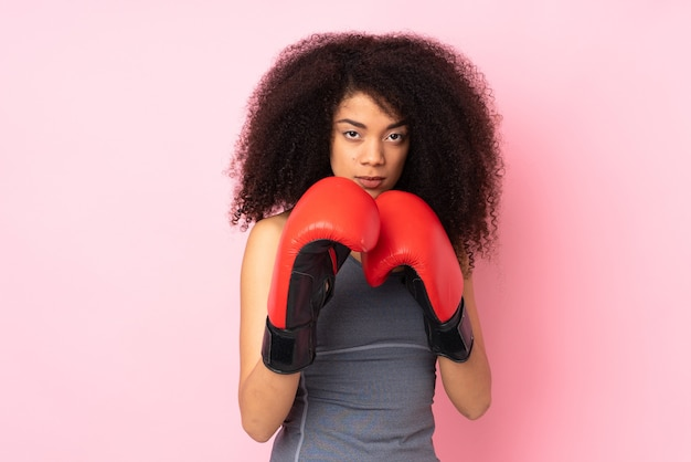 Young african american sport woman isolated on pink with boxing gloves