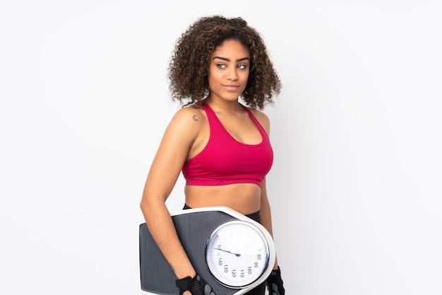 計量機と白い壁に若いアフリカ系アメリカ人スポーツの女性