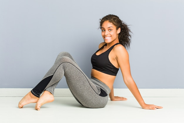 Young african american sporty woman doing rhythmic gymnastics poses