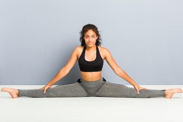 Молодая афро-американская sporty женщина делая представления художественной гимнастики