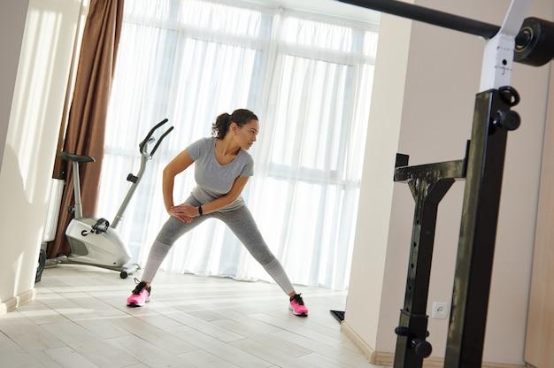 창 표면에 스트레칭 다리를 수행하는 회색 운동복에 젊은 아프리카 계 미국인 스포티 한 여자
