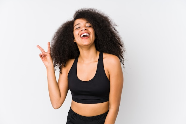 Young african american sporty woman joyful and carefree showing a peace symbol with fingers.