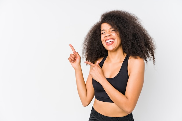 Young african american sporty woman pointing with forefingers to a copy space, expressing excitement and desire.
