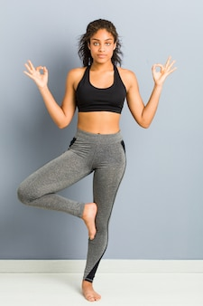 Young african american sporty woman practicing yoga
