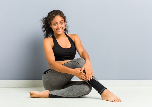 Young african american sporty woman sitting practicing yoga