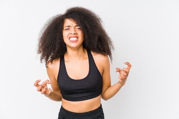 若いアフリカ系アメリカ人のスポーティな女性は、緊張した手で叫んで怒っています。