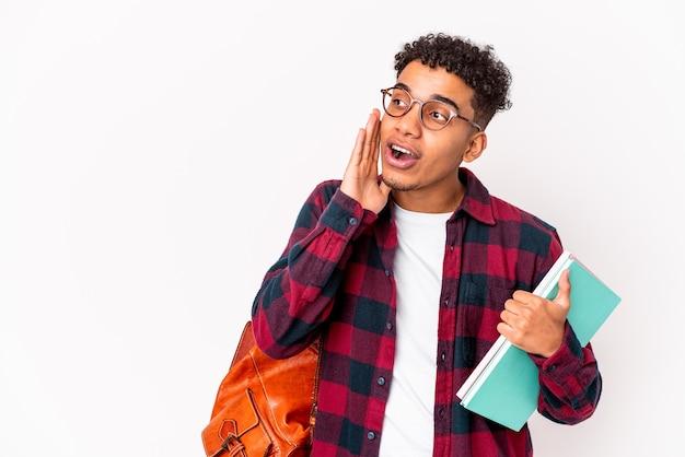 本を持って孤立した若いアフリカ系アメリカ人学生の巻き毛の男は、秘密のホットブレーキニュースを言って脇を見ています