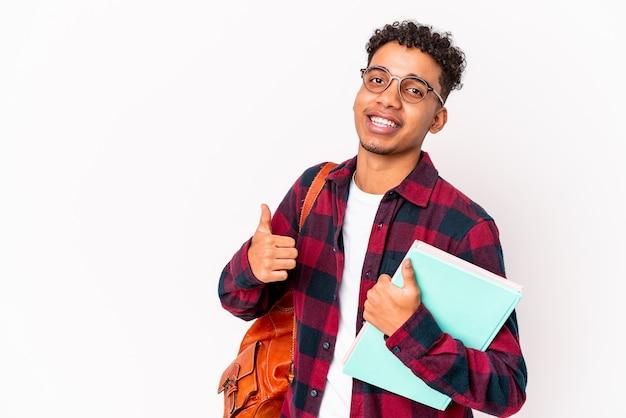 若いアフリカ系アメリカ人の学生の巻き毛の男は、笑顔で親指を上げて本を持って孤立しました