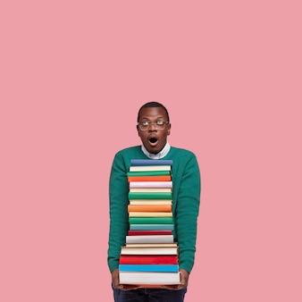 책 더미를 들고 젊은 아프리카 계 미국인 학생