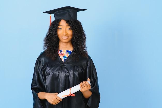 Молодой афро-американский студент в халате бакалавра на цветном фоне
