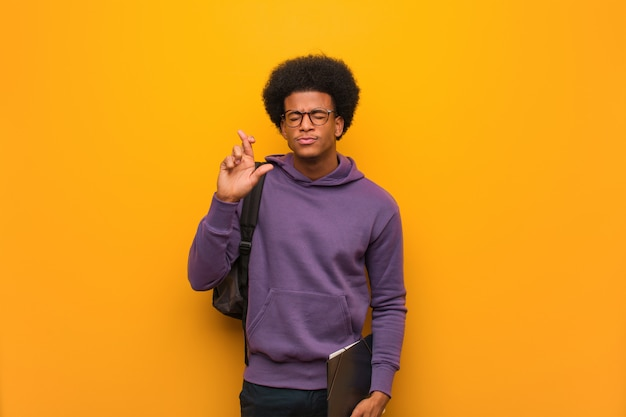 Young african american student man crossing fingers for having luck
