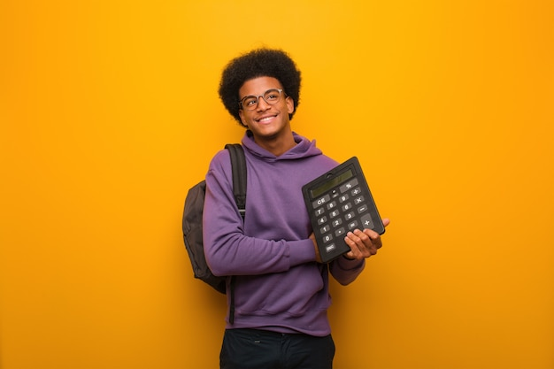 Young african american student man holding a calculator smiling confident and crossing arms, looking up