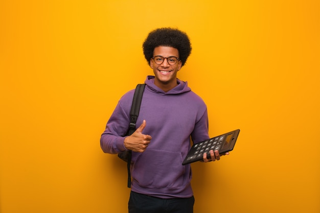 Young african american student man holding a calculator smiling and raising thumb up