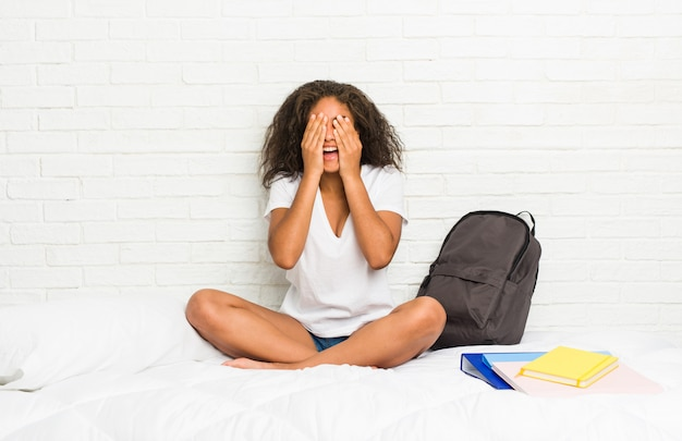 Young african american student woman on the bed covers eyes with hands