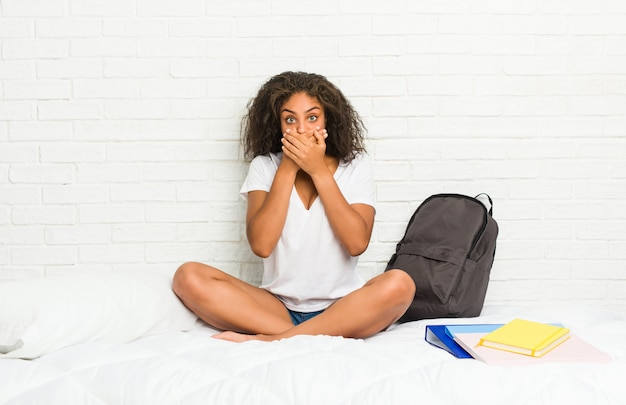 Young african american student woman on the bed shocked covering mouth with hands.