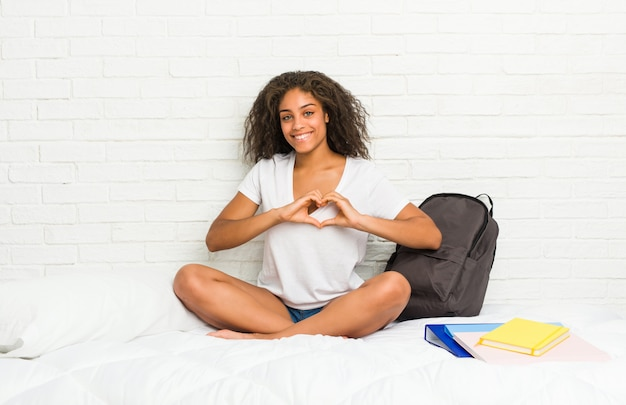 Young african american student woman on the bed smiling and showing a heart shape with hands.