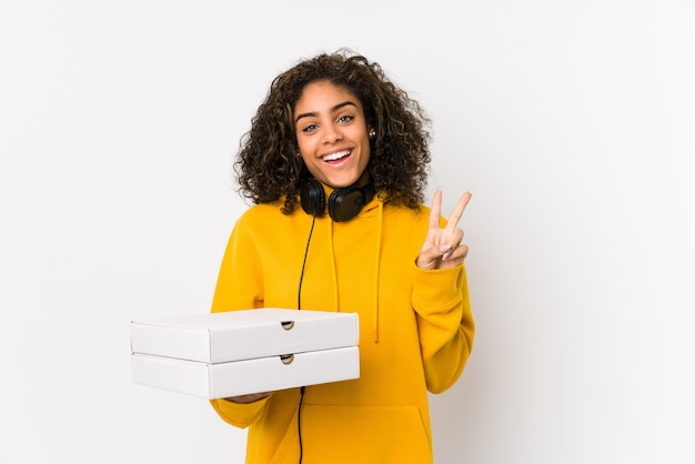 Young african american student woman holding pizzas joyful and carefree showing a peace symbol with fingers.