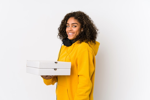 Young african american student woman holding pizzas looks aside smiling, cheerful and pleasant.
