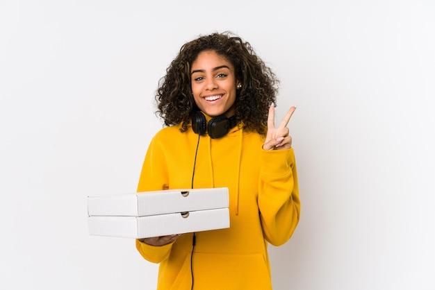 Молодая афро-американская женщина студента держа пиццу показывая номер два с пальцами.