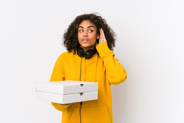 Young african american student woman holding pizzas trying to listening a gossip.