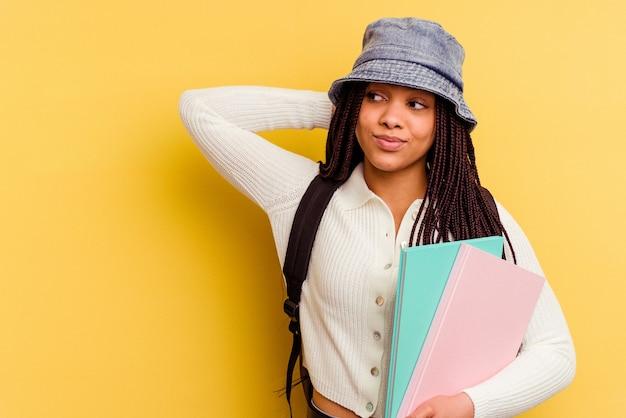 Молодая афро-американская студентка женщина изолирована на желтом трогательном затылке, думая и делая выбор.